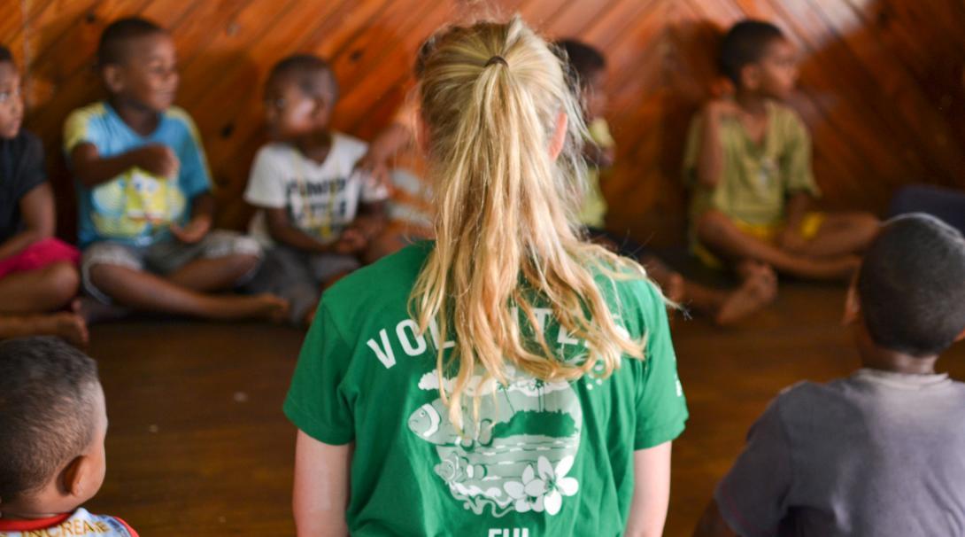 Voluntaria internacional ayudando a niños durante sus clases en Fiyi.
